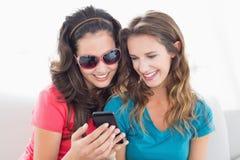 Женские друзья в солнечных очках читая текстовое сообщение Стоковое фото RF
