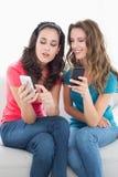Женские друзья в солнечных очках читая текстовое сообщение Стоковые Изображения RF