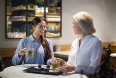 Женские друзья говоря на кафе Стоковое фото RF