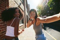 Женские друзья идя на улицу и имея потеху Стоковые Изображения