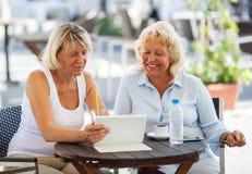 Женские друзья наблюдая что-то на ПК таблетки внутри Стоковая Фотография