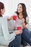 Женские друзья наслаждаясь болтовней над кофе дома Стоковое Изображение
