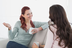 Женские друзья наслаждаясь болтовней над кофе дома Стоковые Изображения RF