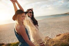Женские друзья наслаждаясь побережьем дня на море Стоковые Изображения RF