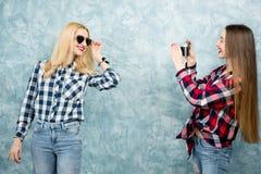 Женские друзья на голубой предпосылке стены Стоковое фото RF