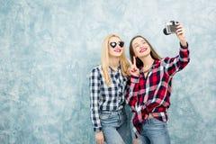 Женские друзья на голубой предпосылке стены Стоковые Изображения