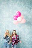 Женские друзья на голубой предпосылке стены Стоковые Фото