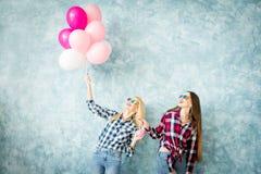 Женские друзья на голубой предпосылке стены Стоковая Фотография