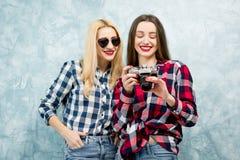 Женские друзья на голубой предпосылке стены Стоковые Фотографии RF