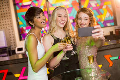 Женские друзья принимая selfie от мобильного телефона пока имеющ шампанское Стоковые Изображения
