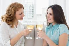 Женские друзья провозглашать бокалы дома Стоковая Фотография RF