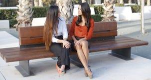 Женские друзья сидя беседовать в городском квадрате Стоковое Фото