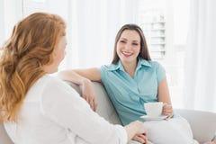 Женские друзья сидя на софе в живущей комнате Стоковые Фотографии RF