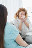 Женские друзья сидя на софе в живущей комнате Стоковая Фотография