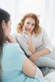 Женские друзья сидя на софе в живущей комнате Стоковое Изображение RF