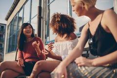 Женские друзья сидя outdoors и говоря Стоковое фото RF