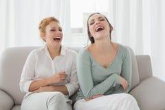 Женские друзья смеясь над пока сидящ на софе в живущей комнате Стоковое Изображение RF