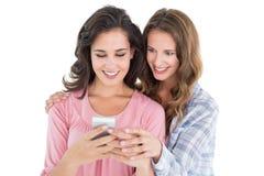 Женские друзья смотря мобильный телефон Стоковое Изображение