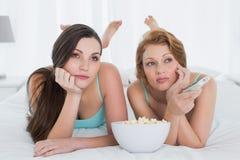 Женские друзья с дистанционным управлением и попкорном в кровати Стоковые Изображения