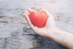 Женские руки давая красные накладные расходы сердца деревянных планок в утре освещают Фильтрованный цвет Винтажный тон Стоковая Фотография RF