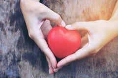 Женские руки давая красные накладные расходы сердца деревянных планок в утре освещают Фильтрованный цвет Винтажный тон Стоковые Изображения