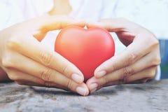 Женские руки давая красные накладные расходы сердца деревянных планок в утре освещают Фильтрованный цвет Винтажный тон Стоковое Фото