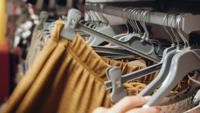 Женские руки бежать на шкафе рельса вешалок одежды и ища платье на магазине одежд сток-видео