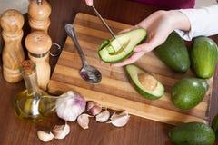 Женские руки варя с авокадоом Стоковое Изображение RF