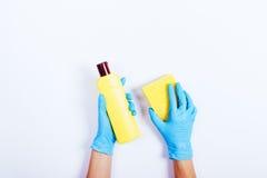 Женские руки в голубых резиновых перчатках держа желтую бутылку de Стоковое Изображение