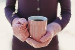 Женские руки в розовых mittens держа чашку с горячими чаем или кофе конец вверх Стоковые Фотографии RF