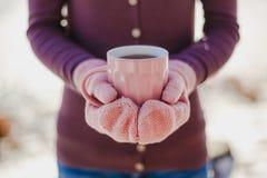 Женские руки в розовых mittens держа чашку с горячими чаем или кофе конец вверх Стоковое фото RF