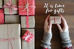 Женские руки в свитере держат подарок на деревянной поверхности Стоковое фото RF