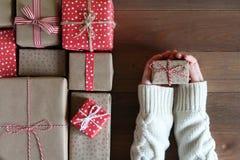 Женские руки в свитере держат подарок на деревянной поверхности Стоковая Фотография