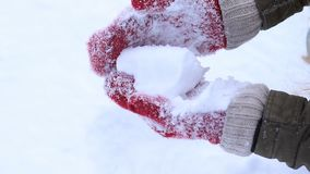Женские руки в связанных mittens делая снежный ком сток-видео