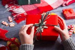 Женские руки в сером цвете связали свитер держа подарочную коробку на Christm Стоковые Изображения RF