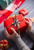 Женские руки в сером цвете связали свитер держа подарочную коробку на Christm Стоковое Изображение