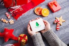 Женские руки в сером цвете связали свитер держа поздравительную открытку на Ch Стоковое Фото