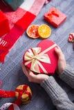 Женские руки в сером цвете связали свитер держа романтичный подарок на Ch Стоковое Изображение