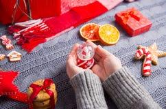 Женские руки в сером цвете связали свитер держа стеклянный снежный ком на c Стоковое Фото