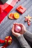 Женские руки в сером цвете связали свитер держа шарик рождества на d Стоковая Фотография