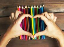 Женские руки в форме сердца на покрашенных карандашах на bac Стоковое Изображение