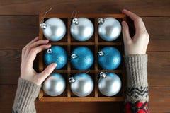 Женские руки в шерстяном свитере держа деревянную коробку с шариками рождества Стоковое Фото