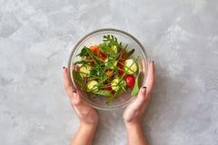Женские руки держат плиту с салатом Стоковые Изображения