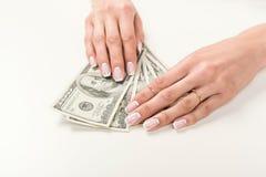 Женские руки держа банкноты доллара на белизне Стоковые Фото