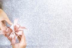 Женские руки держа или давая малую подарочную коробку стоковая фотография rf
