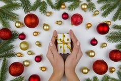 Женские руки держа малую подарочную коробку на белой предпосылке с золотыми и красными шариками рождества и ветвями ели Зима Стоковая Фотография