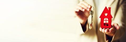 Женские руки держа малый красный дом и ключи Предложение агента недвижимости вы расквартировываете или квартира Страхование собст Стоковая Фотография RF