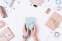 Женские руки держа подарочную коробку с лентой среди deco рождества Стоковые Изображения