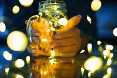 Женские руки держа стеклянную кружку с гирляндами светов Стоковая Фотография RF