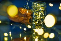 Женские руки держа стеклянную кружку с гирляндами светов Стоковое Изображение RF